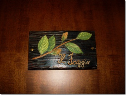 targa di legno sulla porta della Locanda del Biancospino