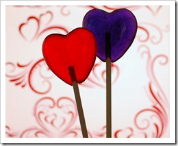 backlit red and purple heart-shaped lollipops in front of red swirly hearts and doodles