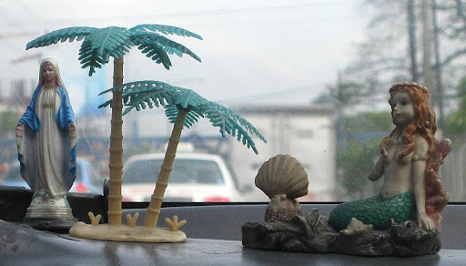the Virgin Mary and a mermaid on a taxi's dashboard