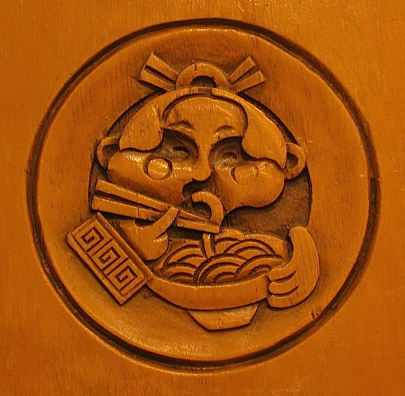 logo of Rai Rai Ken Ramen House and Sushi Bar carved on wooden chair