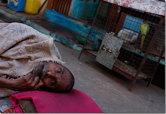 In this Friday, Aug. 7, 2009 photograph, Hira Lal, who has lost the ability to move and hear, lays on a makeshift bed outside his shanty in Bhopal, India. (AP Photo/Saurabh Das)