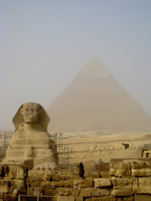 Sphinx in Egypt with a pyramid in the background