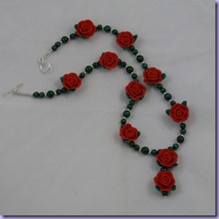 Handmade malachite necklace with blood red polymer clay roses and matching pendant drop made from 2 roses. The spacer beads and toggle clasp are sterling silver. The length is currently 16 inches, but can be changed to suit. The price is £21