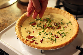 picture of quiche being topped with remaining cheese, bacon, and also chopped chives