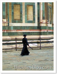 Priest walking beside Duomo in Florence, Italy