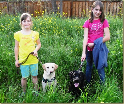 Reyna and Sara and Starling and Emily standing in a field of mustard flowers looking just was cute as can be.
