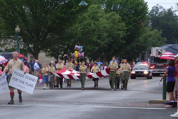 在几位手持美国国旗的老大爷们的引导下,游行队伍来了。我们首先看到的是大幅的星条旗。走在前面的先生手持两块提示牌。路两旁的观众们都自觉起立,以示尊敬。