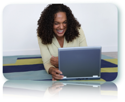 A woman using a laptop and smiling widely.