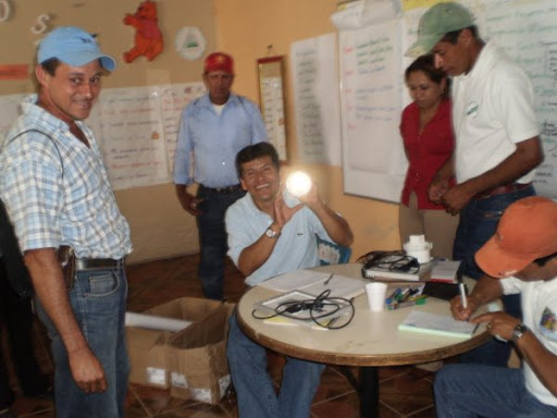 Luis Lanzas, AVODEC dentist holds up a solar lamp, surrounded by AVODEC members.