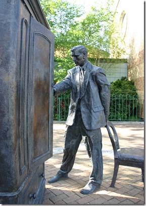 "Statue of C.S. Lewis looking into a wardrobe. Entitled ""The Searcher"" by Ross Wilson displayed in Belfast."