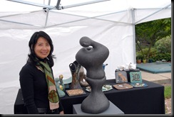 Thien Dao wih her clay sculptors out of the rain.
