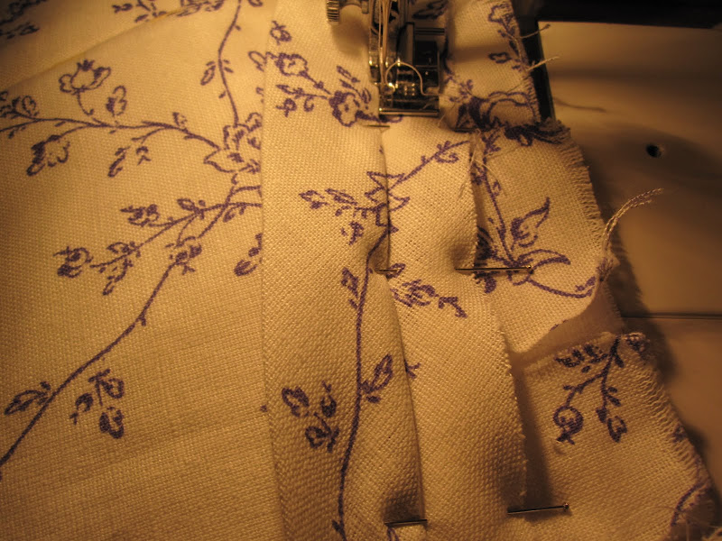 Using the zipper foot to sew the piping on to the bottom of the bodice
