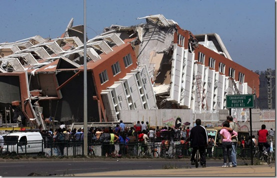 Residents look at a collapsed  building in Concepcion, Chile, Saturday Feb. 27, 2010 after an 8.8-magnitude struck central Chile. The epicenter was 70 miles (115 kilometers) from Concepcion,  Chile's second-largest city.(AP Photo)