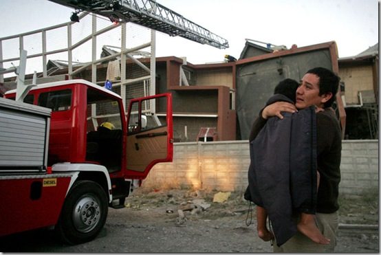 A man carries a child next to a damaged building in Concepcion, Chile, Saturday Feb. 27, 2010 after an 8.8-magnitude struck central Chile. The epicenter was 70 miles (115 kilometers) from Concepcion,  Chile's second-largest city.(AP Photo)