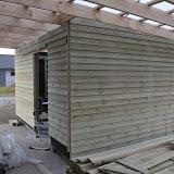 Det næsten færdige redskabsrum - bemærk stakken af træ i forgrunden, det er træterrassen der bare ligger og venter.