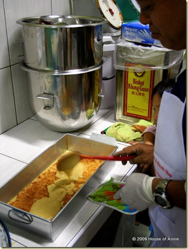 ladling batter onto bottom layer of sarawak layer cake - copyright house of annie