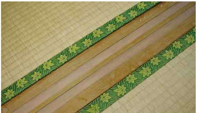 Tatami floor mats with decorative cloth edging fit precisely against a wooden channel for a sliding screen in a traditional Japanese structure. The durable outer covering (tatami omote) of the tatami is tightly woven from stems ofJuncus effusus, soft rush or, as it is known in Japan, igusa.