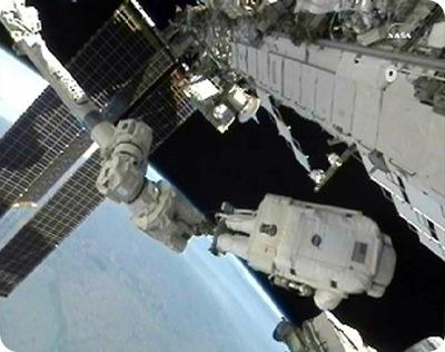 Doug Wheelock, no braço robótico, conserta sistema de refrigeração da ISS (Foto: NASA)