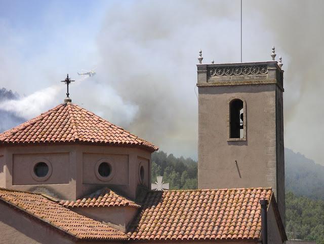 Imatge de la Parr&ograve;quia de La Palma amb el fum de l'incendi de rerafons i un helic&ograve;pter que interv&eacute; en l'incendi. 19 de juny de 2010. <b>Autor: Konfrare Albert</b>