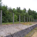 Från höger till vänster: Förbjuden zon, dike, taggtrådshinder, elektrifierad taggtråd, patrullområde. Floden Würm bakom trädridån.