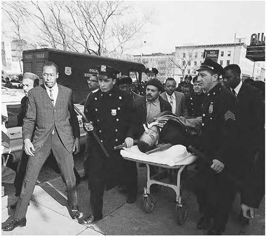 Two policemen in New York City pull a gurney bearing Malcom X after he was downed by an assassin's bullets at a rally on 21 February 1965.