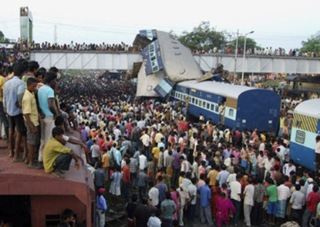 Onlookers stand at the site of a train accident at Sainthia in the eastern Indian state of West Bengal July 19, 2010. A speeding passenger train crashed into another waiting at a station in eastern India early on Monday, killing at least 60 people in India's second major accident in as many months, officials said. REUTERS/Stringer (INDIA - Tags: TRANSPORT DISASTER IMAGES OF THE DAY)