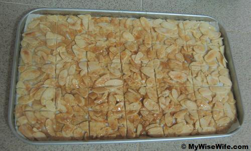 Golden brown caramel almond flakes are lined with knife