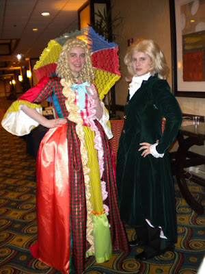 The female Sixth Doctor cosplayer described above faces the camera. To her left is a woman wearing a deep green velvet surcoat over a ruffled blouse: a variant Third Doctor costume.