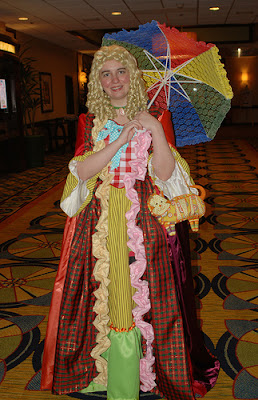 Young woman in a variant Sixth Doctor costume that has been re-imagined as an 18th century ballgown. She is carrying a brightly colored parasol and has a wig of blonde sausage curls.