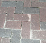 Note sand on surface and empty gaps. Spalding of pavers is clearly evident.