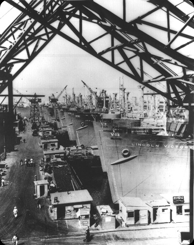 Victory cargo ships are lined up at a US west coast shipyard for final outfitting 1944