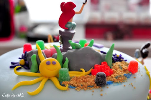 At the back of the cake, behind the rocks is a yellow, purple-eyed octopus.