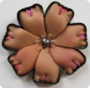 flower design brooch made up of a rosette of faces