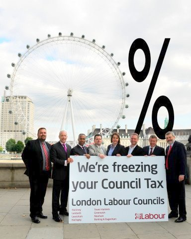 Photo of Labour Council leaders posing by a sign on the North bank of the river Thames 