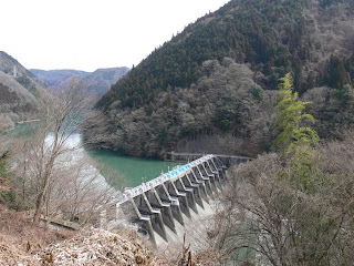 右岸の高台より下流側堤体・ダム湖を望む