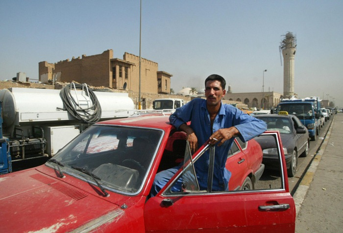 An Iraqi smokes a cigarette out of his car during a traffic jam in central Baghdad, 26 August 2007. Iraq imposed an indefinite curfew on two-wheelers and hand carts in Baghdad and its surrounds yesterday, as thousands of Shiite pilgrims headed to the shrine city of Karbala for a major festival. The curfew came hours after a car bomb in Baghdad's Shiite neighbourhood of Kadhimiyah killed seven people and wounded 30, according to medical and security officials.   AFP PHOTO / ALI YUSSEF (Photo credit should read ALI YUSSEF/AFP/Getty Images)