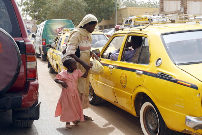 A Displaced Sudanese woman from Darfur holds the hand of her daughter as she begs for money in the traffic jam of Khartoum on February 26, 2008. The deadly conflict in Darfur entered its sixth year today with no solution in sight as Khartoum continued to resist the full deployment of a peacekeeping force amid a fresh wave of bombings. The United Nations said earlier this week that new bombings were endangering thousands of lives in Darfur, seeking reassurances that more civilians would be allowed to flee to join the estimated 2.2 million already displaced by the conflict. AFP PHOTO/ISAM AL-HAJ (Photo credit should read Isam Al-Haj/AFP/Getty Images)