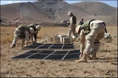U.S. military personnel preparing to deploy portable solar arrays.