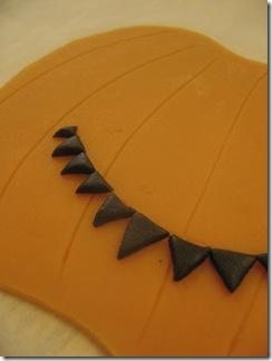 Skär ut små svarta trekanter till mun, näsa och ögon.