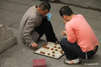 Two Chinese men playing a game in the streets of Quanzhou, China