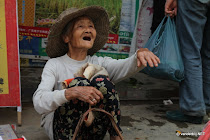 Old Chinese woman begging in the streets of Ful�