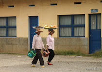 Two Cambodian women carrying goods on large plates on their heads in Battambang