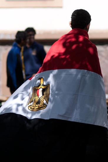 Junger Mann, in ägyptischer Flagge eingehüllt