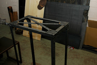 Brooklyn Coffee Table in the beginning stage with the rivet holes drilled and some rivets and the cross braces installed.