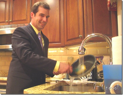 uncool man washing dishes in a suit