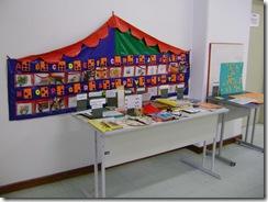 Material tatil para ensino de Braille disposto numa tenda colorida presa na parede. Mesa com recursos para ensino de pessoas com deficiência visual