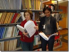 Duas pessoas com livros nas mãos próximas a uma prateleira repleta de livros