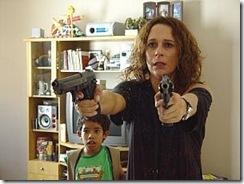 Verônica com uma arma em cada mão. Atrás dela está uma criança