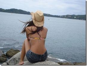 morena fake de costas sentada na beira da praia