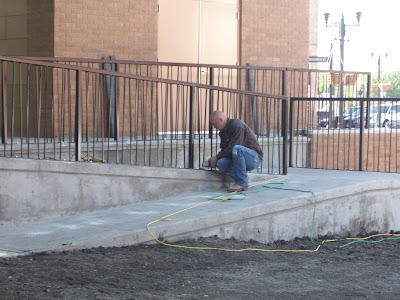 A worker installs railing around the new wheel chair ramp at Washington's Central Park Bandstand (KCII NEWS)